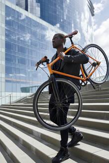 Man carrying his bike - JND00058