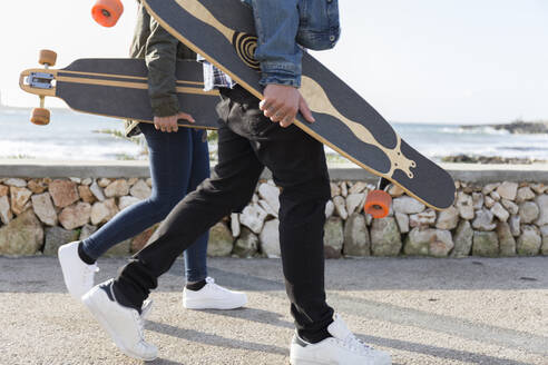 Young couple with longboards walking on promenade, partial view - JPTF00128