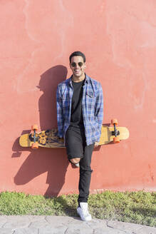 Portrait of laughing young man with longboard standing in front of pink wall - JPTF00131