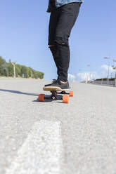 Young man standing on longboard, partial view - JPTF00134