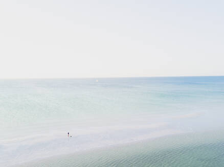 Aerial view or drone view of a beach, the ocean and one young man, Holbox, Mexico. - MMAF00957