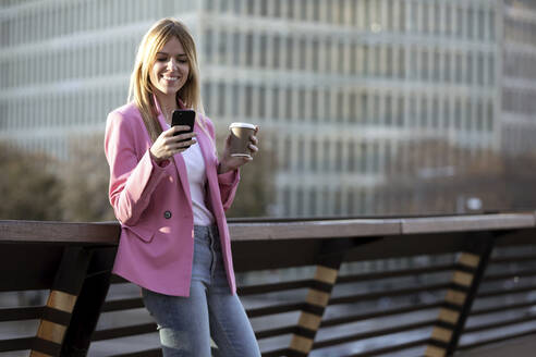 Young businesswoman using smartphone and holding coffee to go - JSRF00194