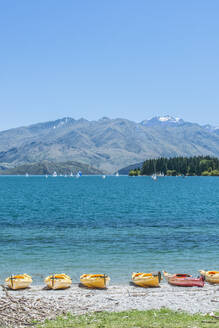 Kayaks docked along beach, Lake Wanaka, Otago, New Zealand - MINF11617