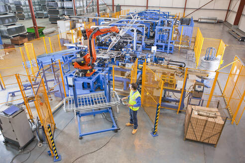 Worker controlling robotic machinery lifting steel fencing on production line in manufacturing plant - JUIF01323