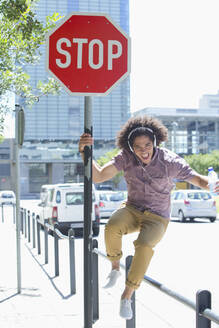 Portrait of enthusiastic young man listening to music on headphones against stop sign in city - JUIF01332