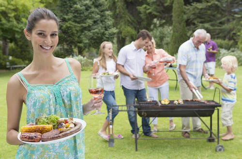 Portrait of smiling woman holding plate of barbecue and glass of wine with family in background - JUIF01335
