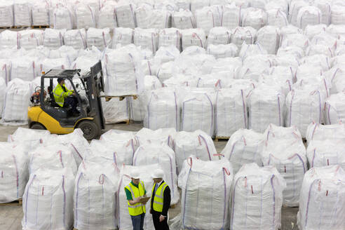 Businessman and workers among large bags of recycled plastic pellets in warehouse - JUIF01347