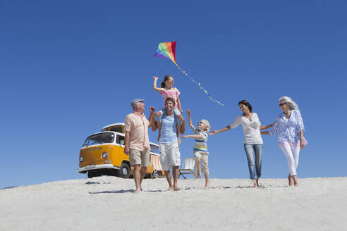 Happy multi-generation family walking with kite on sunny beach with van in background - JUIF01353