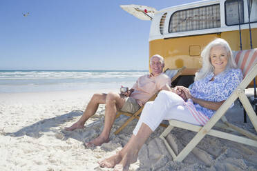Portrait of smiling senior couple sitting on lounge chairs on sunny beach near van - JUIF01356