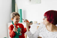 Mother and son having fun while doing crafts at home - JRFF03247