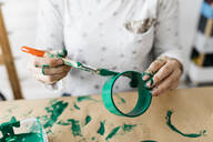Woman's hands painting a roll of cardboard with a green brush - JRFF03250