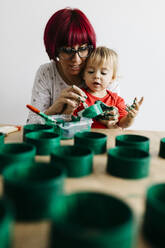 Mother and daughter doing crafts at home, painting cardboard rolls to make a Christmas tree - JRFF03256