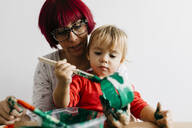 Mother and daughter doing crafts at home painting cardboard roll - JRFF03259