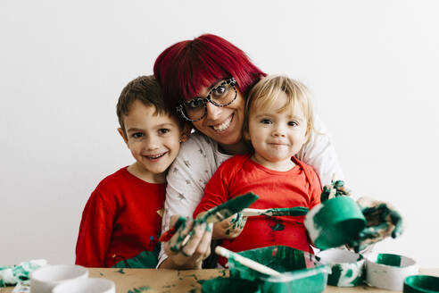 Mother with her children doing crafts at home and painting with green. - JRFF03262