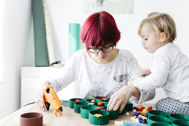 Mother and daughter doing crafts at home with accessories to make a Christmas tree - JRFF03265