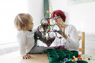 Mother and daughter doing crafts at home with accessories to make a Christmas tree - JRFF03268