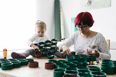 Mother and daughter doing crafts at home with accessories to make a Christmas tree - JRFF03271
