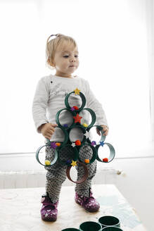 Little girl with a Christmas tree made with painted cardboard rolls and accessories - JRFF03274