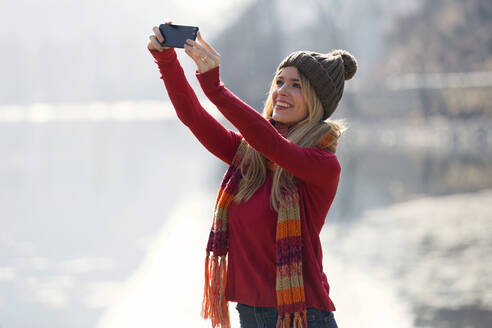Young blond woman taking a selfie at a lake in winter - JSRF00207