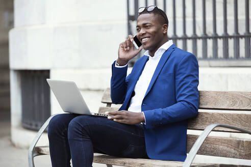 Portrait of handsome young business man using his mobile phone while using laptop in the street. - JSRF00237