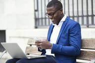 Young businessman wearing blue suit jacket sitting on bench and using smartphone - JSRF00240