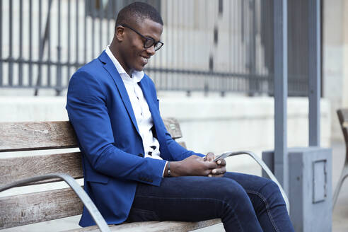 Young businessman wearing blue suit jacket sitting on bench and using smartphone - JSRF00243