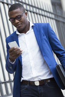 Portrait of handsome young business man using his mobile phone in the street. - JSRF00246