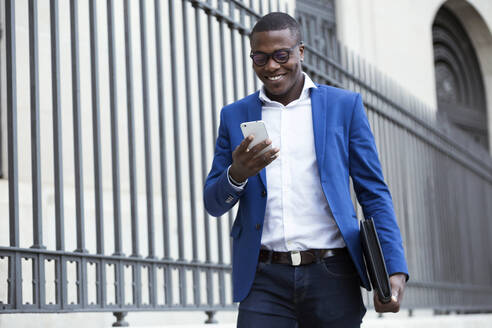 Young businessman wearing blue suit jacket and using smartphone - JSRF00249