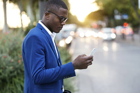Young businessman wearing blue suit jacket and using smartphone - JSRF00258