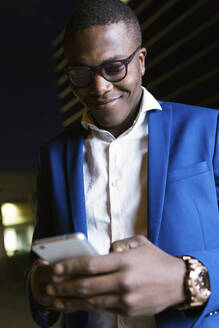 Young businessman wearing blue suit jacket and using smartphone at night - JSRF00267