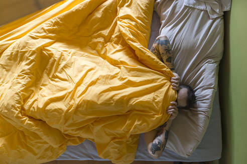 Tattooed man lying in bed, blanket over his face - JPTF00141