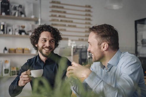 Two businessmen having a meeting in a coffee shop - KNSF05990