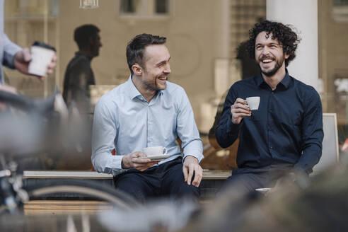 Friends sitting in front of coffee shop, talking, drinking coffee - KNSF05993