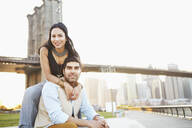 Indian couple smiling by bridge, New York, New York, United States - BLEF06739