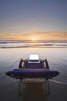 Laptop on deck chair overlooking sunset on beach - MINF12298