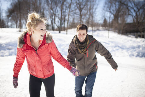 Caucasian couple ice skating on frozen lake - MINF12304