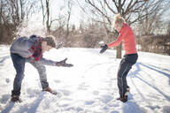 Caucasian couple having snowball fight - MINF12307