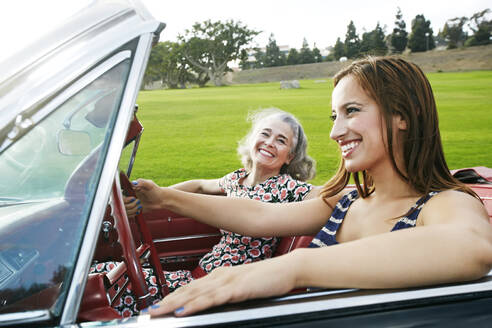 Mother and daughter driving in classic convertible - BLEF06844