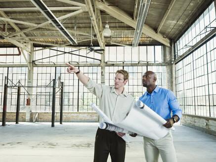 Businessmen reading blueprints in empty warehouse - BLEF06868