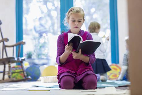 Caucasian girl reading book on floor - BLEF06925