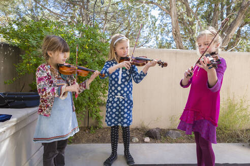 Girls playing violin outdoors - BLEF06949
