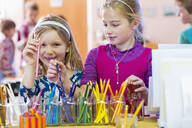 Caucasian girls choosing multicolor pencils in classroom - BLEF06958