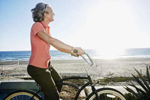 Caucasian woman riding bicycle near beach - BLEF06976