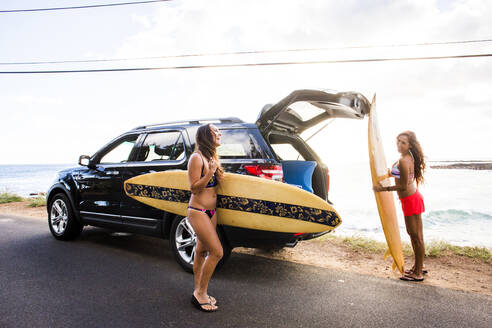 Surfers unloading surfboards from car near beach - BLEF06991