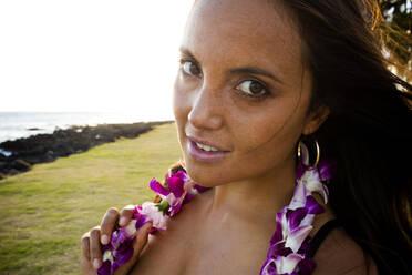 Caucasian woman wearing flower lei near ocean - BLEF06994