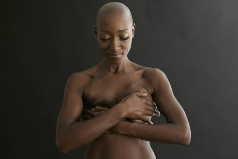 Nude African American cancer survivor covering her breasts - BLEF07018