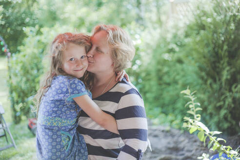 Mother kissing her daughter outdoors - IHF00105