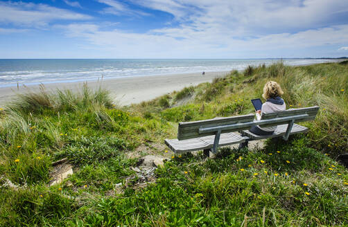 Woman sitting on a bench using tablet at Foxton beach, Kapiti Coast, North island, New Zealand - RUNF02686