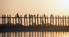 People walking on elevated wooden walkway at sunset - MINF12426