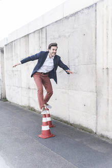 Young man balancing on traffic cones in front of concrete wall - UUF17823